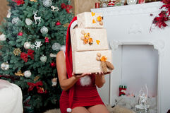 Natale interno La ragazza tiene le scatole Fotografie Stock Libere da Diritti