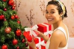 Natale La donna di colore sta tenendo il contenitore di regalo rosso Albero di Natale Immagine Stock