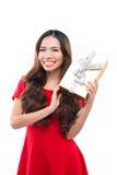 Natale, natale, inverno, concetto di felicità - donna sorridente in vestito rosso con il contenitore di regalo Immagini Stock