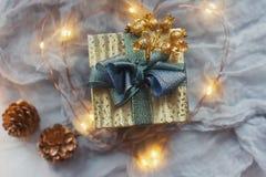 Natale o nuovo anno presente nel contenitore di regalo dorato con il nastro blu, in coni dorati e nel cuore principale Fotografia Stock