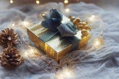 Natale o nuovo anno presente nel contenitore di regalo dorato con il nastro blu, in coni dorati e nel cuore principale Immagine Stock Libera da Diritti
