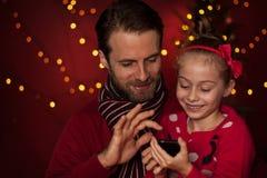 Natale - padre e figlia che giocano gioco sul telefono cellulare Immagini Stock Libere da Diritti