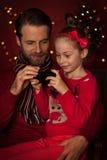 Natale - padre e figlia che giocano gioco sul telefono cellulare Fotografia Stock Libera da Diritti