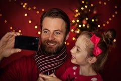 Natale - padre e figlia che prendono la foto 'del selfie' sul telefono cellulare Immagini Stock