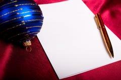 Natale. Penna, documento e sfera blu. Immagine Stock