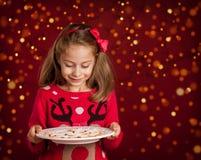 Natale - piatto dei biscotti della tenuta della ragazza del bambino su rosso scuro con le luci Fotografia Stock Libera da Diritti