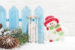 Natale pupazzo di neve e giocattoli della slitta e ramo di albero dell'abete fotografie stock