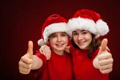 Natale ragazza e ragazzo del tempo con Santa Claus Hat che mostra segno GIUSTO fotografie stock libere da diritti