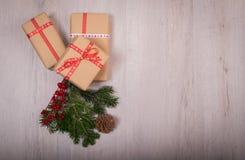 Natale regalo ed ornamenti con il pino ed il cono sopra un legno Fotografie Stock Libere da Diritti