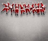 Natale Santa che appende sulla corda. Fotografie Stock