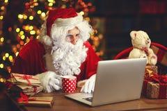 Natale Santa Claus con la lettera della lettura del computer portatile Immagini Stock Libere da Diritti