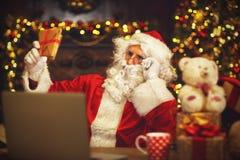 Natale Santa Claus con la lettera della lettura del computer portatile Fotografia Stock Libera da Diritti
