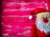 Natale Santa Claus su un fondo del rosa di legno variegato Immagini Stock Libere da Diritti