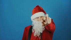 Natale, uomo come un dito indice di manifestazioni di Santa nella macchina fotografica, nuovo anno, su fondo blu stock footage