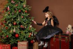 Natale, vacanza di inverno e concetto della gente - la bambina in costume nero di angelo si siede su un tronco vicino ad un alber Immagini Stock