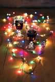 Natale: vino rosso sulla tavola con le luci variopinte Immagine Stock