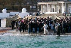 Natação de Peopls na água gelado o Mar Negro durante o esmagamento (batismo santamente) na tradição ortodoxo Fotos de Stock Royalty Free