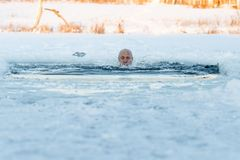 Natação do inverno Homem a um gelo-furo Fotografia de Stock Royalty Free