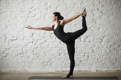 年轻Natarajasana姿势的信奉瑜伽者可爱的妇女,白色顶楼bac 库存图片