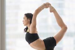 Natarajasana姿势的年轻可爱的妇女反对地板窗口 免版税库存图片