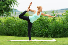 妇女在绿草做瑜伽本质上, Natarajasana 免版税库存照片