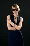 Natasha. Young attractive woman standing in dark blue dress on a black background in sunglasses Royalty Free Stock Images