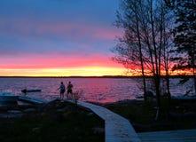 Natation allante de personnes outre du dock avec le beau rose et l'orange de coucher du soleil Images stock