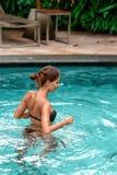 Natation bronz?e mince de femme ? la piscine Repos et station thermale Fin vers le haut photo stock