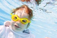Natation d'enfant dans la piscine sous-marine Photo stock