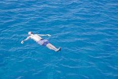 Natation d'homme en mer sur le sien de retour image stock