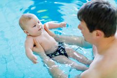 Natation d'une cinquantaine d'années heureuse de père avec le bébé adorable mignon dans la piscine Photographie stock libre de droits