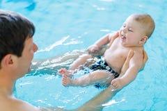 Natation d'une cinquantaine d'années heureuse de père avec le bébé adorable mignon dans la piscine Photo stock