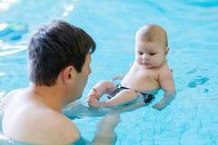 Natation d'une cinquantaine d'années heureuse de père avec le bébé adorable mignon dans la piscine Image libre de droits