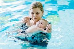 Natation d'une cinquantaine d'années heureuse de mère avec le bébé adorable mignon dans la piscine Photographie stock libre de droits