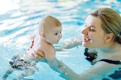 Natation d'une cinquantaine d'années heureuse de mère avec le bébé adorable mignon dans la piscine Image libre de droits