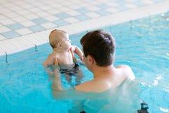 Natation d'une cinquantaine d'années heureuse de père avec le bébé adorable mignon dans la piscine Images stock