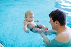 Natation d'une cinquantaine d'années heureuse de père avec le bébé adorable mignon dans la piscine Photographie stock