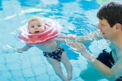 Natation d'une cinquantaine d'années heureuse de père avec le bébé adorable mignon dans la piscine Image stock