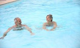 Natation de couples dans la piscine Photographie stock libre de droits