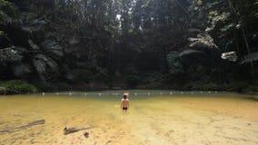 Natation de femme dans la piscine naturelle multicolore avec la cascade scénique dans la forêt tropicale des collines parc nation banque de vidéos