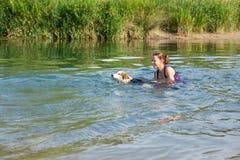 Natation de femme et de chien dans une rivière, une étude et un stagiaire dans W photos stock