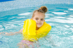 Natation de fille dans la piscine dans le gilet de sauvetage Photos libres de droits