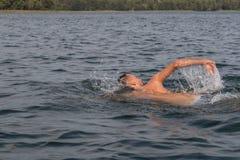 Natation de jeune homme dans le lac photos stock