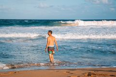 Natation de jeune homme dans les vagues énormes photo stock