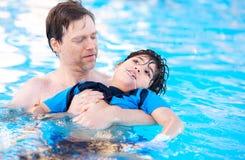 Natation de père dans la piscine avec l'enfant handicapé photo libre de droits