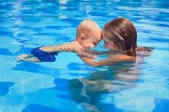 Natation de petit enfant dans la piscine avec la mère images libres de droits