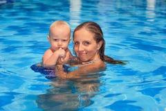 Natation de petit enfant dans la piscine avec la mère photographie stock libre de droits
