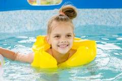 Natation gaie de fille dans le gilet de natation de piscine Photo stock