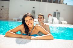 Natation gaie de sourire de femme dans une piscine claire un jour ensoleillé Avoir l'amusement sur la réception au bord de la pis Photographie stock libre de droits