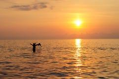 Natation heureuse de père et d'enfant en mer au beau coucher du soleil coloré Images libres de droits